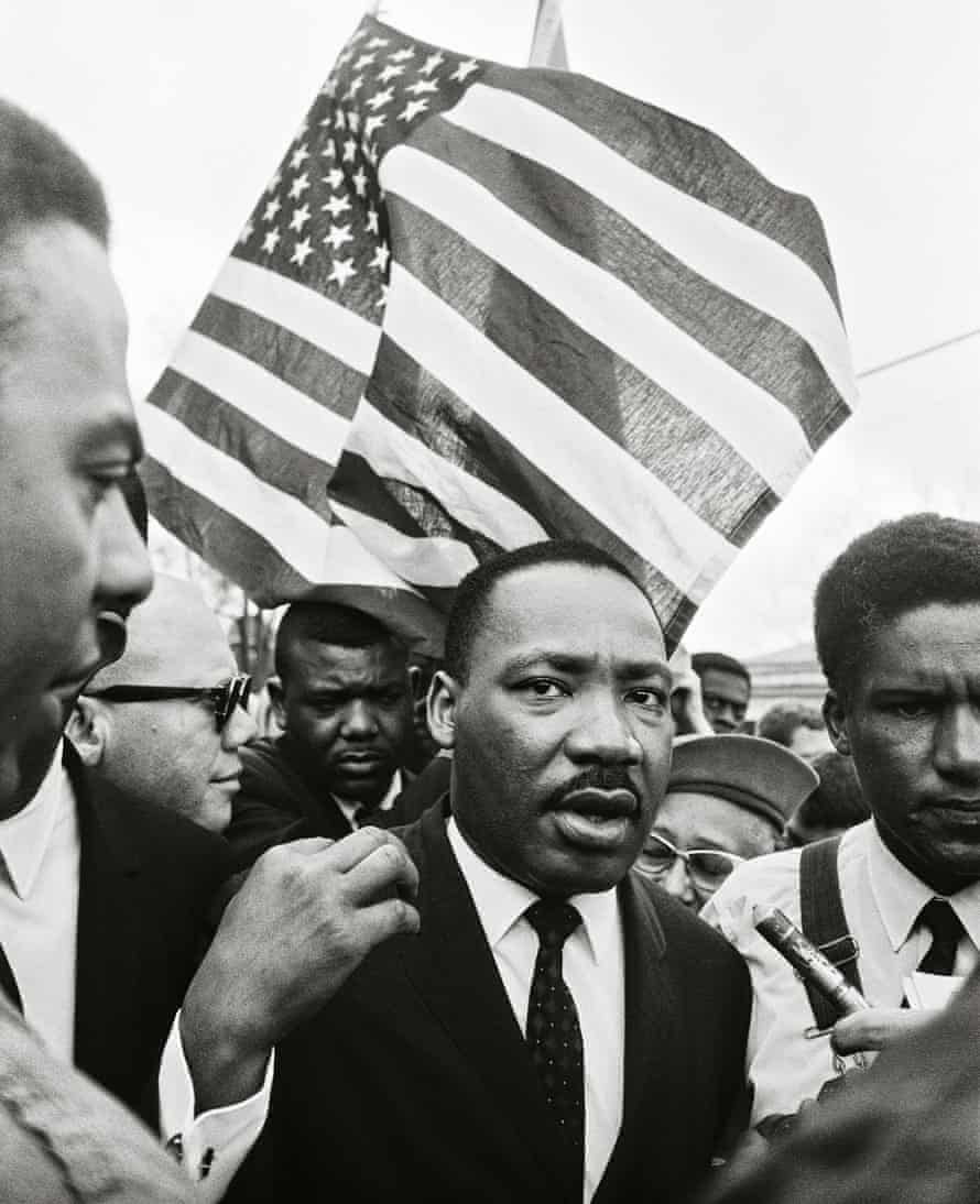 Ralph Abernathy (rear) and Dr. King lead the way on the road to Montgomery. The American flag was a natural symbol for a movement that called on the nation to live up to its principles. 1965 © 2017 Steve Schapiro
