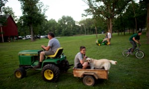Derek Nordman, 16, holds his golden retriever, Logan, 3, while his uncle Paul Kittle drives them in a tractor at the Jacktown Tractor Engine Show on 15 July 2017.