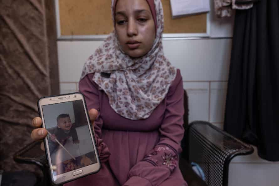 May Al-Masri holds a picture of her son Yasser, killed by a rocket outside her home. She was pregnant at the time.
