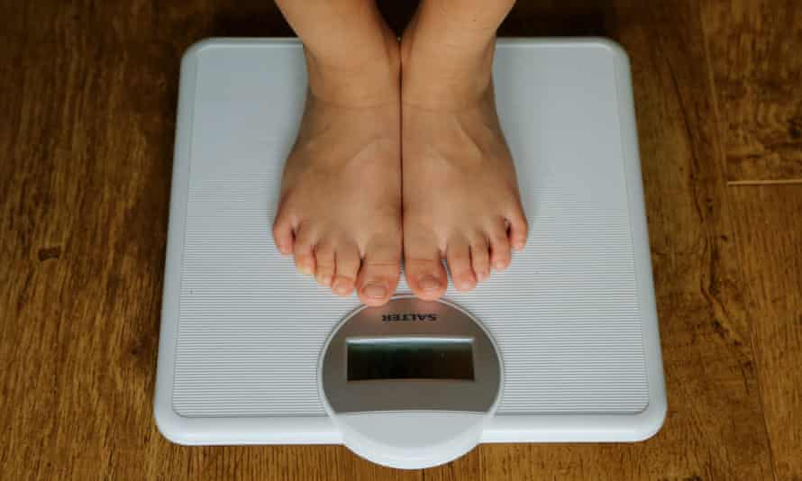 Someone standing on weighing scales (lower legs, bare feet only visible)