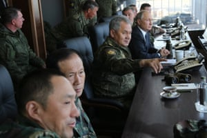 Russia's defence minister, Sergei Shoigu, and the president, Vladimir Putin, watch the war games with military personnel