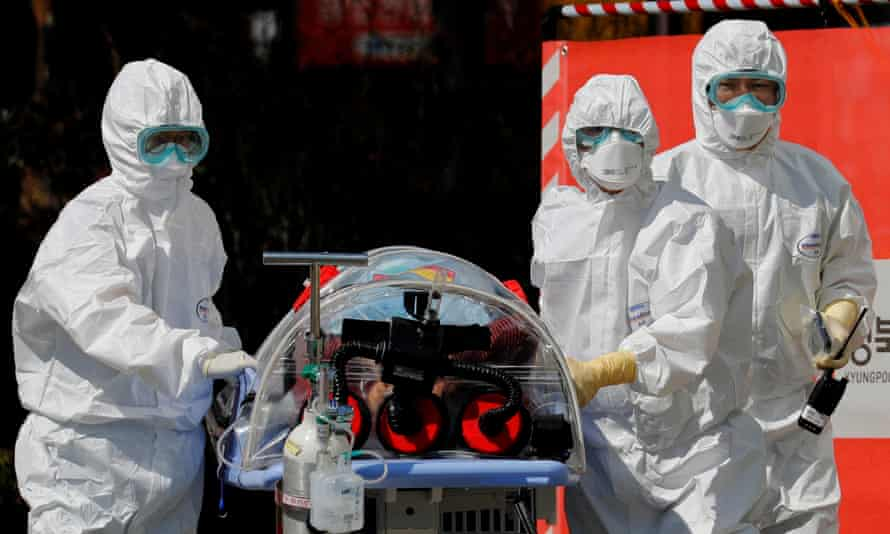 Medical workers transport a patient who is suspected of having Covid-19, in Daegu, South Korea.