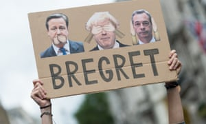 A protester holds up a sign featuring David Cameron, Boris Johnson and Nigel Farage