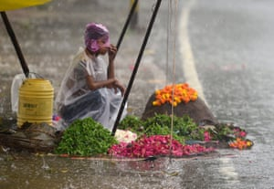 A boy covers himself with a plastic sheet as he waits for customers at a flower stall during heavy rain in Allahabad in India