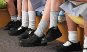 The feet of students sitting in a row in a classroom