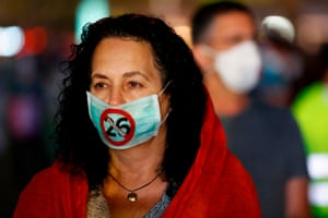 Tel Aviv, Israel A physician swearing a surgical mask bearing a slogan expressing dissatisfaction with work demands exceeding twenty six hours work per day in hospitals, stands with other demonstrators in Rabin square