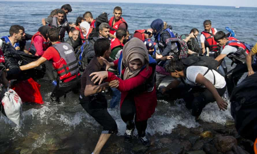 Migrants and refugees arrive on a dinghy after crossing from Turkey to Lesbos island, Greece.