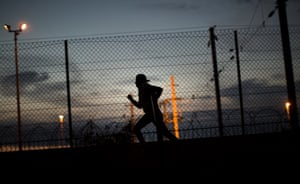 A migrant runs after crossing a fence as he attempts to access the Channel Tunnel in Calais, France