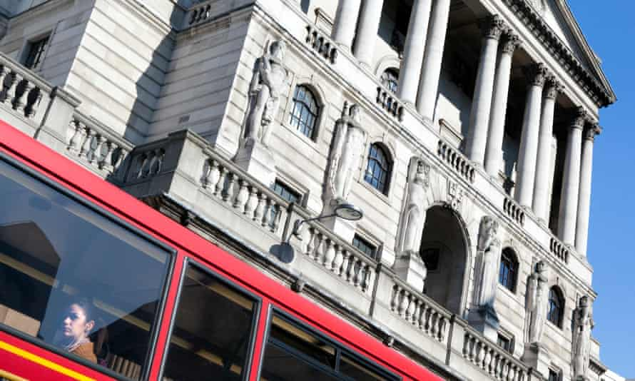 A red London bus passes the Bank of England building