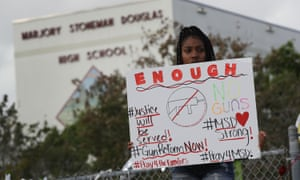Tyra Heman, a senior at Marjory Stoneman Douglas High School, holds a sign that reads 'Enough'.