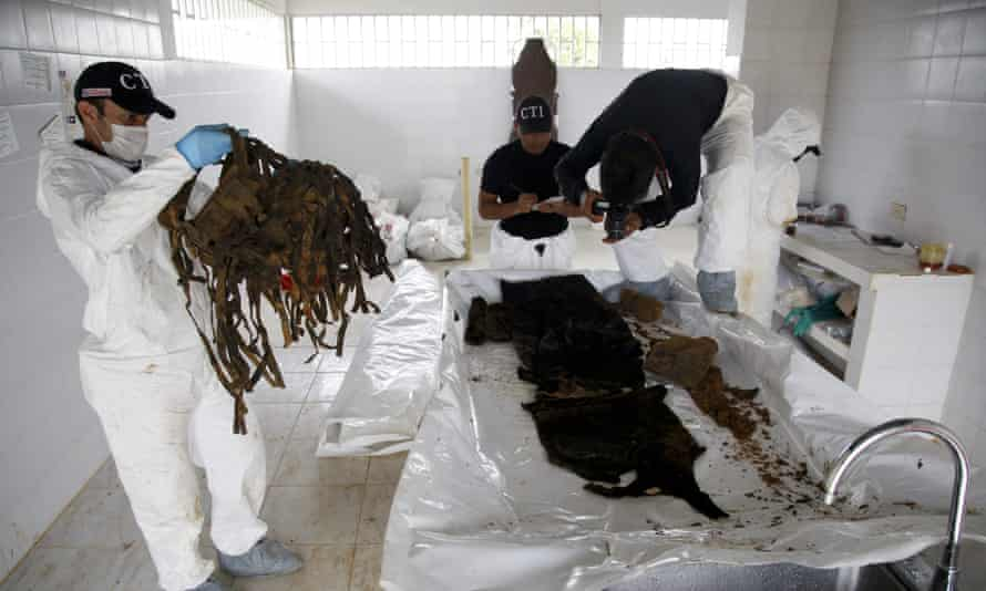Forensic anthropologist Diego Casallas, left, holds a backpack he found inside a body bag with an unidentified cadaver, unearthed at the cemetery in La Macarena, Colombia.