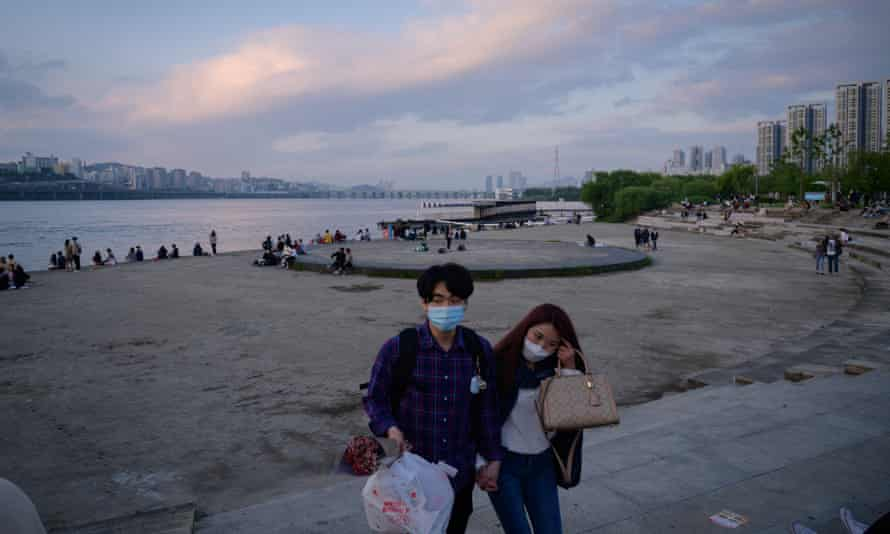 People wearing face masks amid concerns over Covid-19 novel coronavirus walk through a park before the Han river in Seoul