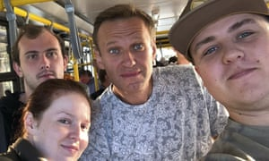 Three men and a woman posing on a bus