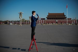 A television journalist stands on a ladder in Beijing