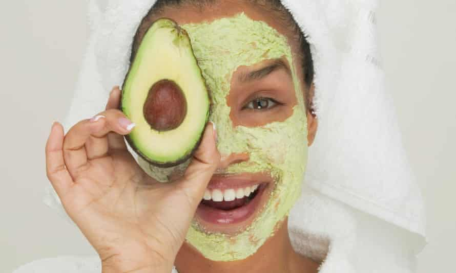 A young woman wearing a facial mask holding a slice of avocado