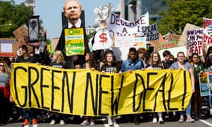 Crowd of protesters march with large 'Green New Deal' banner and placards