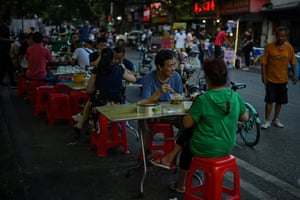 People eat on the street during the afternoon in front of a small restaurant