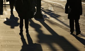 Silhouettes of people walking on a street in Manchester