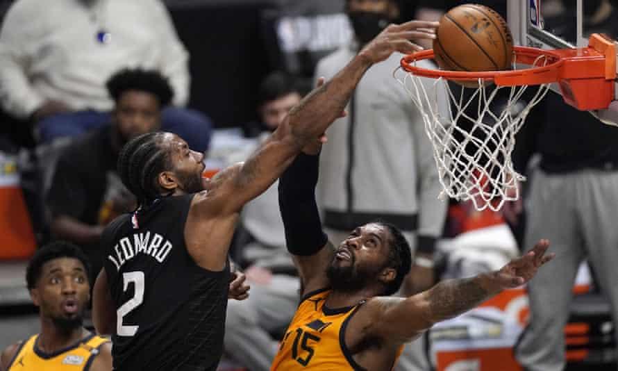 Kawhi Leonard dunks over Utah Jazz center Derrick Favors