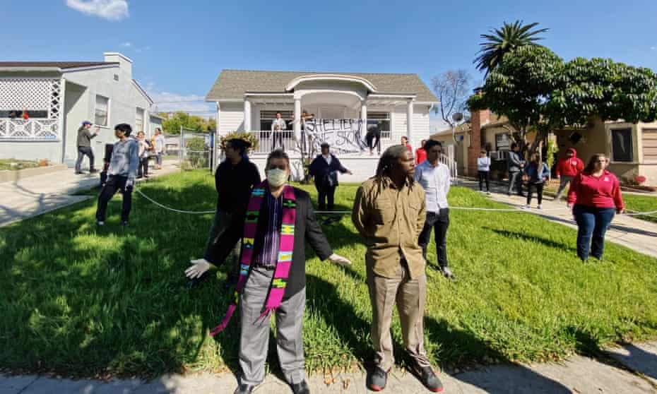 Members of Reclaiming Our Homes stand guard on the first day of a home takeover in LA.