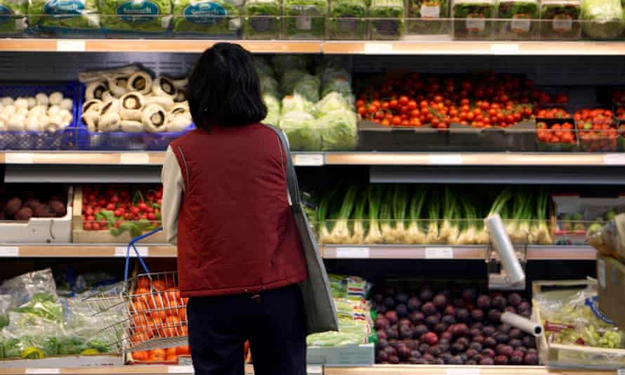 woman in front of vegetable display in a supermarket