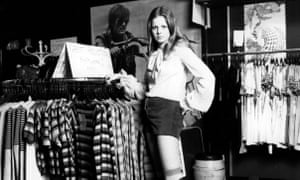 A teenager wearing hot pants and striped knee length socks in a clothes boutique, 1972.