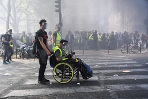 A protester in a wheelchair sits amidst teargas during clashes with police after thousands of gilets jaunes protesters took to the streets for a 23rd week of anti-government demonstrations.