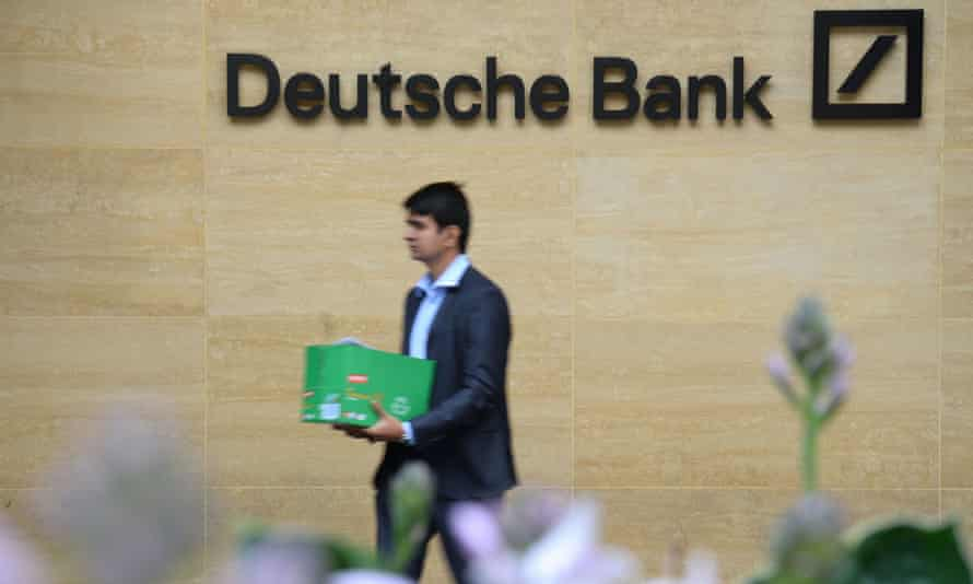 A man carries a box as he leaves a London office of Deutsche Bank which has confirmed plans to cut 18,000 positions across its global business.