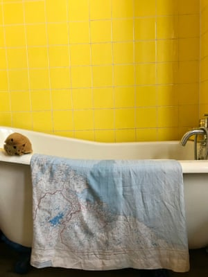 Orsola de Castro's map dress draped over the side of a bath with a yellow tiled wall behind.
