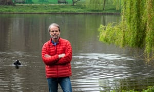 Erling Kagge in jeans and a red jacket, in the countryside, a lake behind him