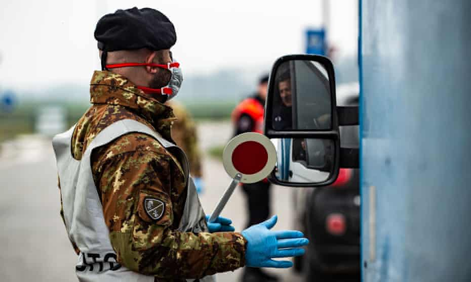 A man in military uniform and blue disposable gloves next to a vehicle at a check point in Lodi, Lombardy