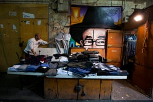 A shop owner prepares to close his store next to a portrait of Rabbi Shlomo Ben David Lakein