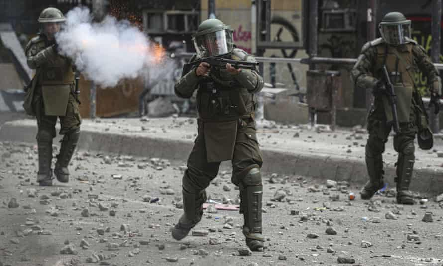 Police shoot tear gas and a shotgun during clashes with anti-government protesters in Santiago, Chile, in November. A UN team has called for the immediate end to the indiscriminate use of anti-riot shotguns.