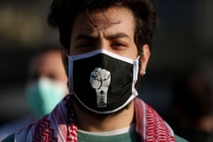 Beirut, Lebanon  A protester wears a mask bearing a fist, the sign of the anti-government movement, during a demonstration about the country's economic crisis