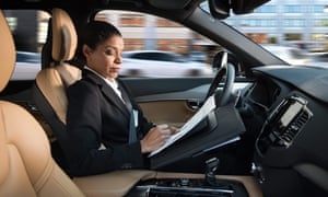 woman working in driver's seat of moving car
