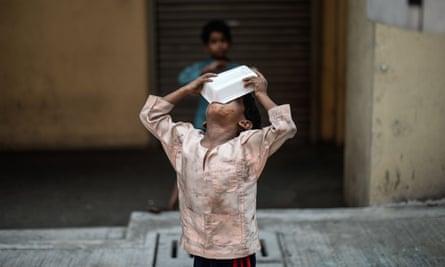 A homeless child eats food on a street in Kuala Lumpur