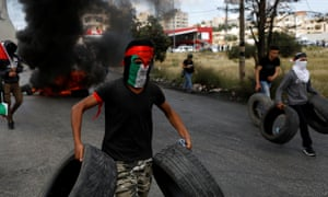 Palestinian demonstrator carries tires to be burnt during a protest marking the 70th anniversary of Nakba, near the Jewish settlement of Beit El, near Ramallah