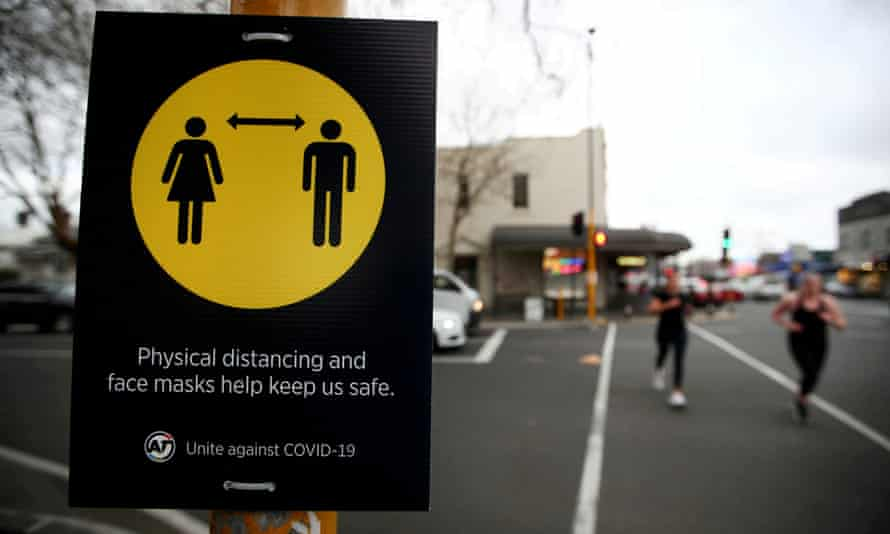 People jog past a social distancing sign in Auckland, New Zealand