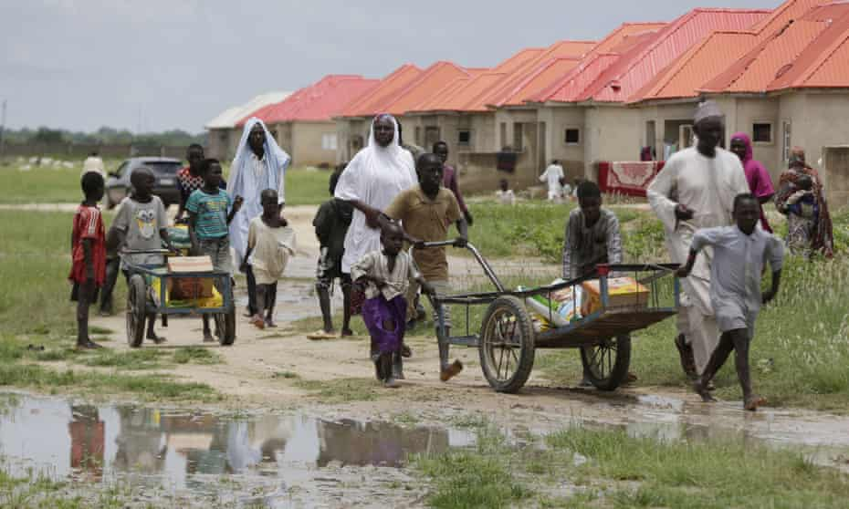 Families displaced by Islamist extremists wheel food handed out to them at a camp in Maiduguri, Nigeria.