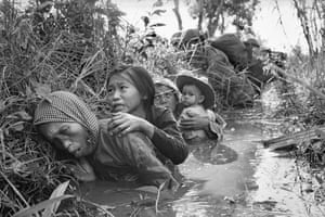 Women and children crouch in a muddy canal as they take cover from intense Viet Cong fire, January 1, 1966