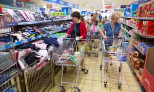 Customers push shopping carts as they walk through the shopping aisles inside a supermarket