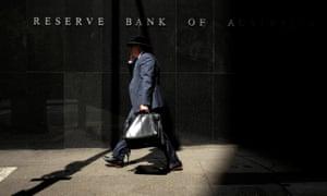 A Sydney businessman walks into the light outside the Reserve Bank of Australia (RBA)