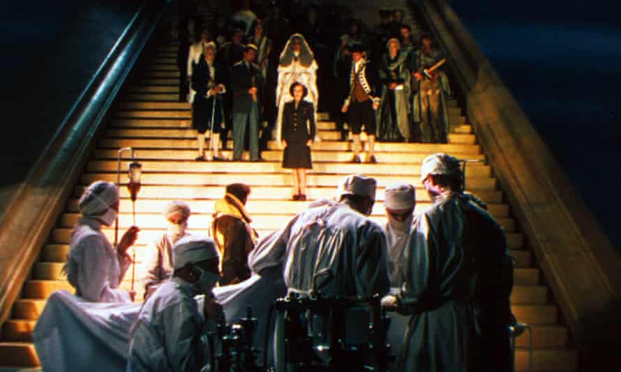 Hunter, as June, looks down from the stairway to Niven, as Peter, who stands by the operating table.