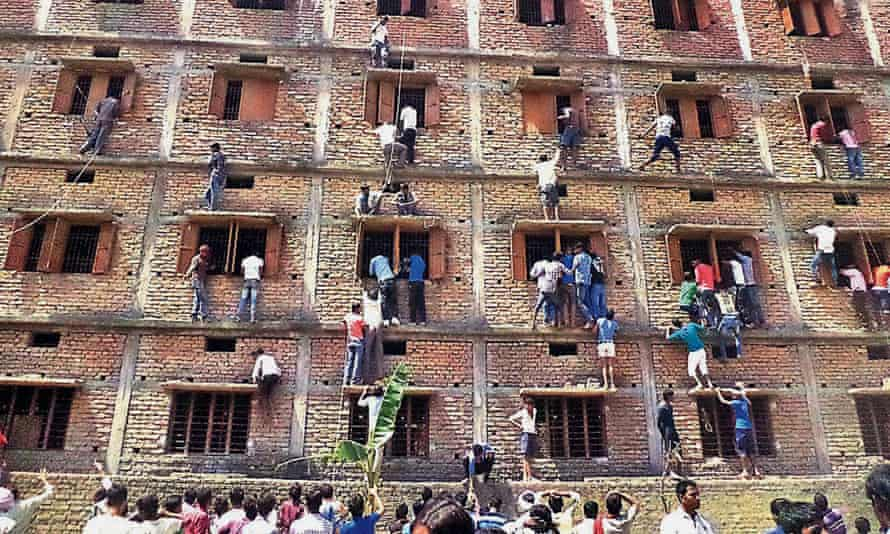 People climb the wall of an exam centre in March. India suffers from huge problems with fake degrees and cheating in crucial exams.