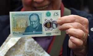 Looking on the bright side … a woman holds up a new £5 banknote bearing the image of Winston Churchill at its unveiling on 2 June 2016.