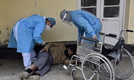 Health workers prepare to help a patient allegedly infected with the new coronavirus, who was found in the yard, get on a wheelchair, in the Clinics hospital in La Paz last week.