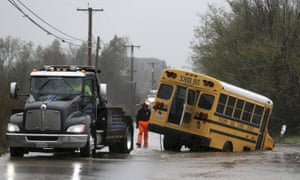 A tow truck crew pulls a schoolbus out of high water in Petaluma, California, on Wednesday.