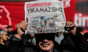 A protester holds up a copy of an edition of Cumhuriyet