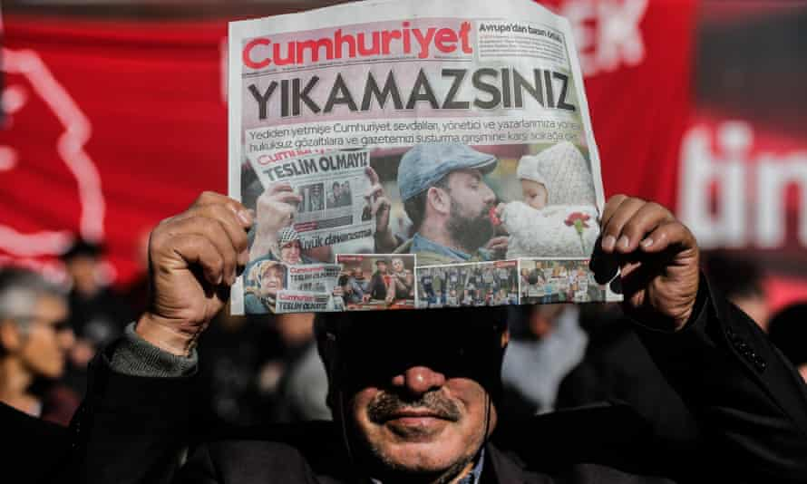 A protester holds a copy of the latest edition of Cumhuriyet during a demonstration outside the newspaper's headquarters in Istanbul on 2 November.