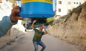 Creative shot showing a bucket held above a boy's head